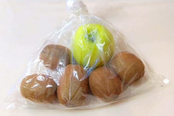 りんごとキウイをビニール袋に入れて追熟させている写真。